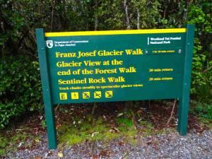 Südinsel, Wanderwege am Franz Josef Gletscher. Ein grün-gelbes Hinweisschild beschreibt die verschiedene Strecken zum Franz Josef Gletscher