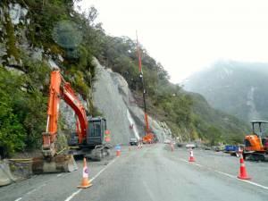 Südinsel, Bauarbeiten bei den Diana Falls auf dem Haast Pass. Bauarbeiter hängen an den Wänden eines Felsen und versuchen die Straße vor herabfallenden Steinen zu schützen, ein orangefarbener Bagger steht im Vordergrund