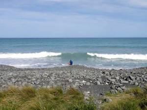 Neuseeland | Südinsel, Henning einsam am Strand in Kaikoura mit Blick auf das blaue Meer sitzend, Vulkangestein im Vordergrund