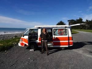 Neuseeland | Südinsel, Campen am Meatworks Camping Platz in Kaikoura. Karin steht vor unserem Hippie Camper mit Blick auf das Meer bei Sonnenschein