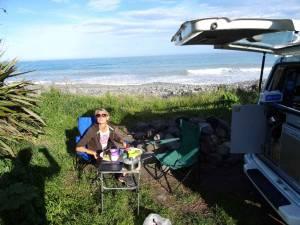 Neuseeland | Südinsel, Abendessen in Kaikoura auf dem Meatworks Campingplatz. Karin sitzt in einem Klappstuhl am gedeckten Tisch mit Blick auf das Meer