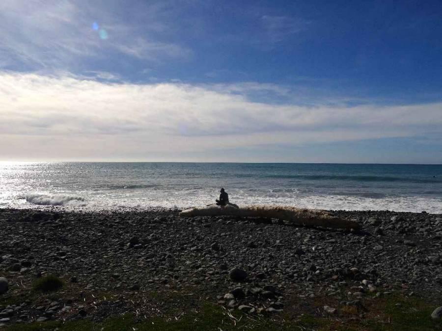 Neuseeland | Südinsel, der Strand am Meatworks Campingplatz in Kaikoura. Karin sitzt weit entfernt auf einem Stein mit Blick auf das Meer und wartet auf den Sonnenuntergang