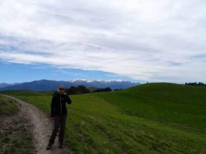 Neuseeland | Südinsel, Wanderung des Peninsula Walkway in Kaikoura. Karin mmit Sonnenbrille auf grüner Wiese mit schneebedeckten Bergen im Hintergrund