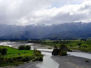 Neuseeland | Südinsel, Panorama des Lewis Pass auf Fluss, schneebedeckte Berge, grüne Wiesen und Büsche