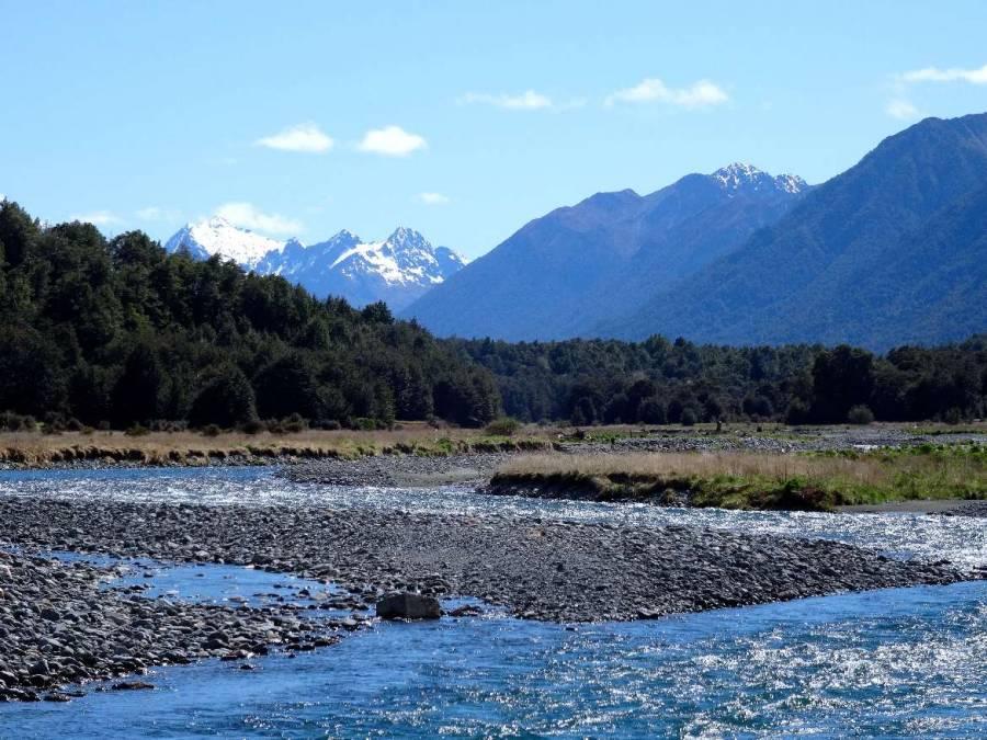 Neuseeland | Südinsel, Cascade Creek Camping am Milford Sound. Blick auf den Fluss, grüne Tannen und schneebedeckte Berge