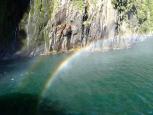 Neuseeland | Südinsel Milford Sound Cruise. Ein Regenbogen spiegelt sich in der Gischt des Wasserfalls vor Felsen und dem Meer aus Sicht der Fähre