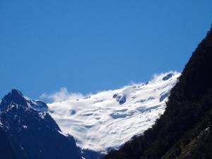 Neuseeland | Südinsel, Schneeberge aus Sicht der Milford Sound Cruise vor blauem Himmel bei Sonnenschein
