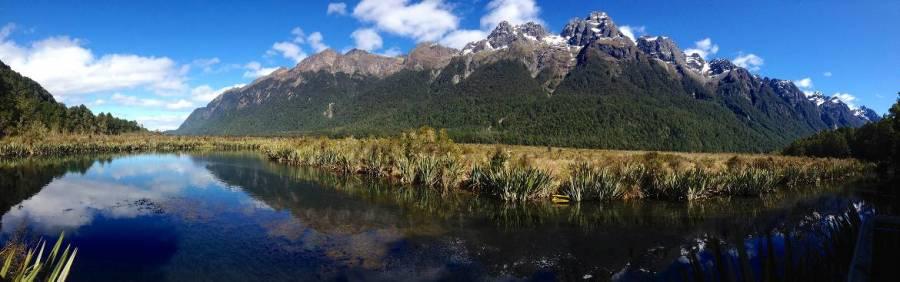 Neuseeland | Südinsel, Mirror Lake auf dem Weg zum Milford Sound. Schneebedeckte Bergspitzen und grüne Gräser spiegeln sich bei herrlich blauen Himmel im Wasser des Sees