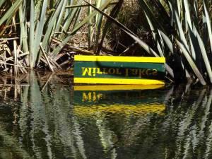 Neuseeland | Südinsel, Mirror Lake auf dem Weg zum Milford Sound. Ein grün-gelbes Schild mit der auf dem Kopf stehenden Aufschrift Mirror Lake aus der Nähe. Im Wasser die korrekte Spiegelung Mirror Lake
