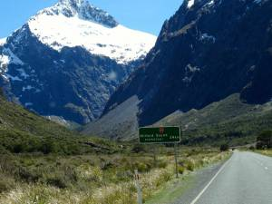 Neuseeland | Südinsel, Straße zum Milford Sound. Grünes Schild mit dem Hinweis noch 24 km vor schneebedeckten hohen Bergen