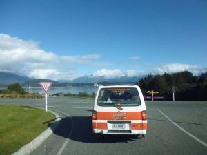 Neuseeland | Südinsel, Weg nach Te Anau und Milford Sound. Unser Hippie von hinten an einer Straßenkreuzung mit Blick auf den Lake Te Anau bei blauem Himmel