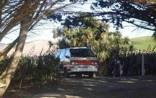 Neuseeland | Südinsel, Camping am Mordaki Beach. Unser Hippie direkt am Strand umgeben von Palmen an einem unserer Tipps der Top kostenlosen Campingplätze