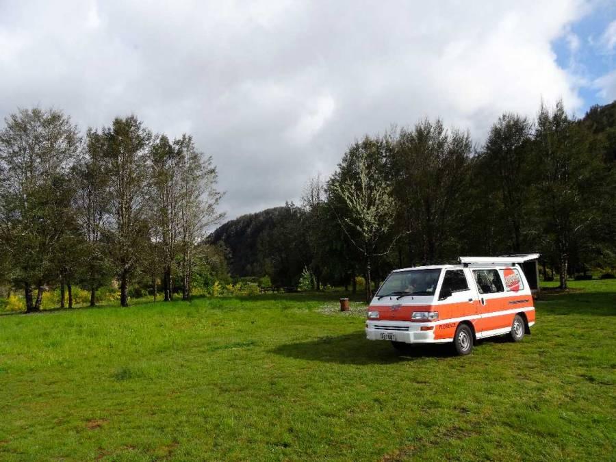Neuseeland | Südinsel, Nelson Creek Campingplatz. Unser orange weißer Hippie Camper steht mitten im Grünen