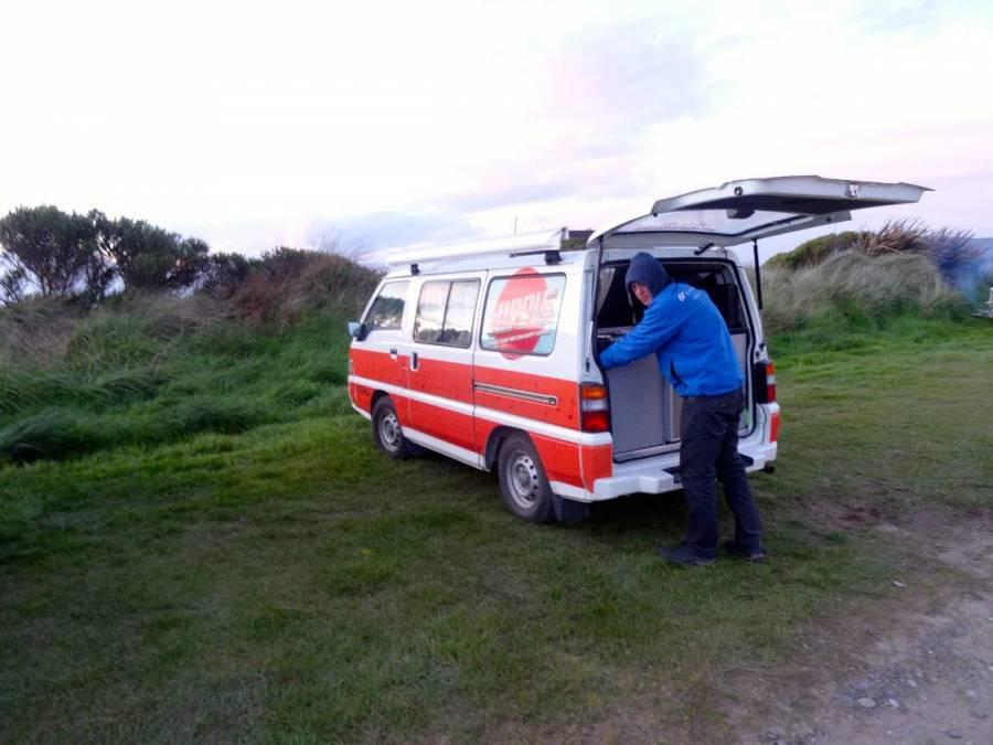 Neuseeland | Südinsel, Camping bei der Orepuki Monkey Island Picnic Area. Henning bei offener Heckklappe vor unserem Hippie Camper bei tosendem Wind