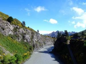 Neuseeland | Südinsel, in der Nähe von Reefton auf dem Weg zum Lewis Pass. Fluss. Berge, gelbe Blüten auf grünen Wiesen, blauer Himmel