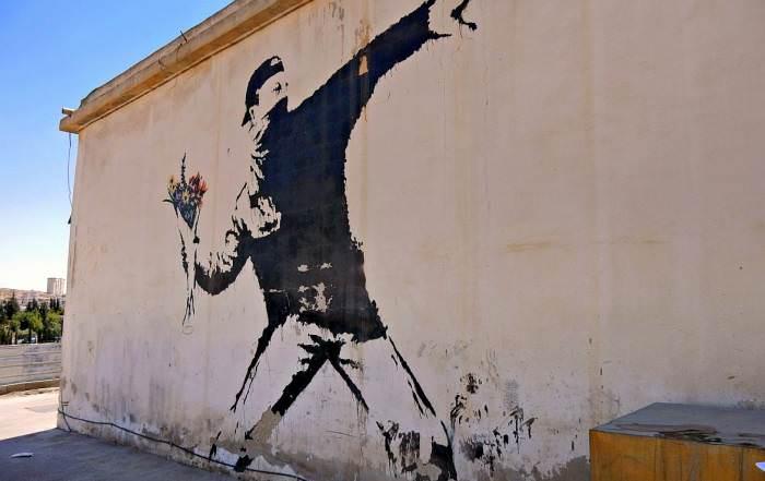 Palästina | Vermumter Mann scheint einen Molotowcocktail werfen zu wollen, hat aber einen Blumenstrauß stattdessen in der Hand