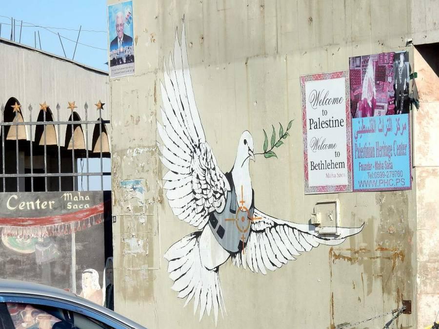 Palästina | Friedenstaube mit schusssicherer Weste im Fadenkreuz neben einem Willkommen-Schild der Stadt Bethlehem
