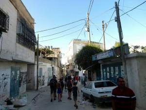 Palästina | Straße mit viel Müll und einem kaputten Autowrack