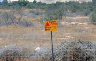 Palästina | Gelbes Schild warnt vor einem abgezäunten Minenfeld