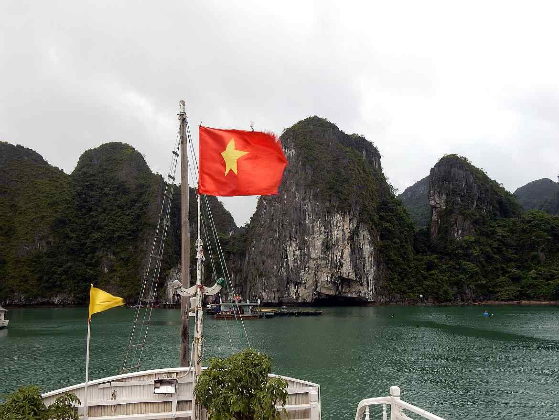Vietnam | Norden, Panorama vom Boot unserer Ha Long Bay Cruise. Die vietnamesische Fahne am Masten, Karstberge im Hintergrund