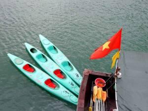 Vietnam | Norden, Kanus in der Ha Long Bay. Blick von oben auf 3 türkisfarbene Kanus, orangefarbene Paddel und eine vietnamesische Flagge