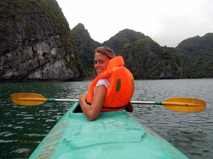 Vietnam | Norden, Mit dem Kanu geht´s zur Luon Cave in der Ha Long Bay. Karin vorne im türkisfarbenen Kanu mit einem gelben Paddel in der Hand, den Blick lächelnd zurückgerichtet mitten in einer Bucht fotografiert vom hinteren Sitz im Kanu