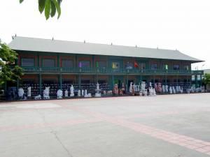 Vietnam | Norden, auf dem Weh in die Ha Long Bay. Souvenir Shop für Touristen. Außenansicht des grün-roten Souvenir-Ladens mit einigen weißen Steinstatuen im Vordergrund