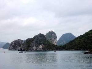 Vietnam | Norden, Tempel in der Ha Long Bay auf urwaldbewachsenen Karstfelsen auf einem Berg gelegen. Der Himmel ist bewölkt, ein paar Fischerboote im Vordergrund im schimmernden tiefgrünen Wasser