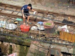 Vietnam | Norden, Hanoi, auch Abwaschen kann man auf den Gleisen. Ein Mann beim Reinigen seines Geschirrs