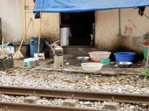 Vietnam | Norden, Wasser kochen an den Bahngleisen in Hanoi. Ein Kessel mit Wasser wird vor dem Eingang zu einem Wohnhaus direkt am Gleis erhitz. Verschieden farbige Schüsseln stehen daneben