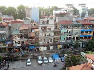 Vietnam | Norden, Eindrücke der Wohnungen an den Bahngleisen in Hanoi. EIn mehrstöckiges Haus mit verschiedenen Wohnungen direkt an den Bahngleisen