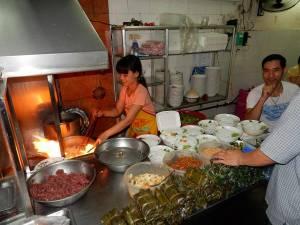 Vietnam | Norden, Bun Bo Nam Bo Restaurant in Hanoi. EIne Vietnamesin vor ihrem Wok kochend, Reisnudeln, Rindfleisch und Gewürze im Vordergrund