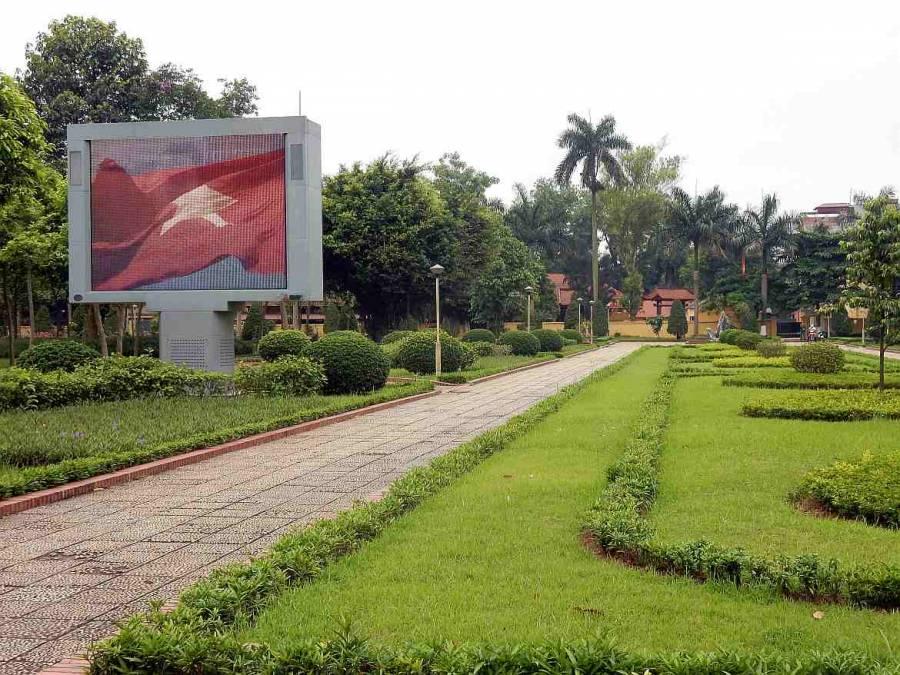 Vietnam | Norden, Hanoi. Der Weg zum Eingang des Ho Chi Minh Museum durch einen Gartenanlage die vietnamesische Flagge auf einem großen Bildschirm links vom Weg