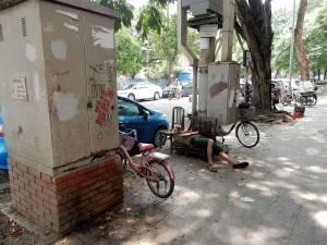 Vietnam | Norden, Mittagsschlaf vietnamesischer Art in Hanoi. Ein Mann auf zwei Stühlen mitten auf dem Bürgersteig