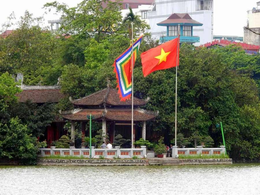 Vietnam | Norden, Hanoi. Der Ngoc Son Tempel inmitten des Hoan Kiem See. die vietnamesische Flagge und ein buntes Wappen im Vordergrund