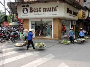 Vietnam | Norden, Gemüseverkäufer in Hanoi. Vor einem Kleidungsgeschäft mit dem Namen Best Mum stehen 4 Frauen mit Spitzhüten und verkaufen Gemüse