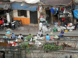 Vietnam | Norden, Wohnen entlang der Bahngleise in Hanoi. Eine Familie sitzt mit verschiedenen Arbeiten auf den Gleisen vor ihrem vollgemüllten Haus. Der Weg entlang der Abhn gehört zu unseren Top-Tipps zu Sehenswürdigkeiten in Vietnam