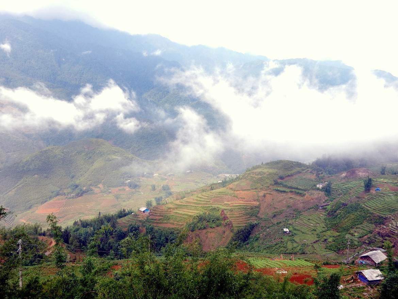 Norden, Reisterrassen und Bergdörfer in der Umgebung von Sa Pa. Panoramablick von oben mit tief hängenden Wolken. Die Tour ist einer unserer Tipps & Highlights in Nordvietnam