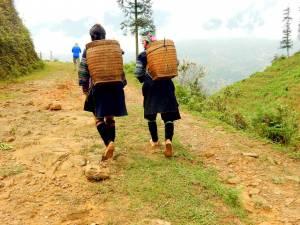 Vietnam | Norden, stete Begleitung auf unserer Tour durch die Bergdörfer Sa Pa´s. Zwei Einheimische mit Kiepen auf dem Rucken laufen vor uns