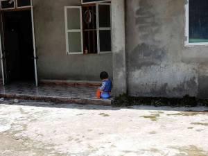 Norden Vietnam, Sapa. Ohne Worte! Ein Mädchen sitzt vor eienem Hauseingang mitten in den Bergen bei Sa Pa auf einem blauen Pott