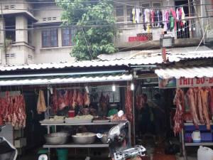 Vietnam | Süden, Metzger in Ho Chi Minh City. Blick auf das aufgehängte rohe Fleisch vor einem Metzgerladen