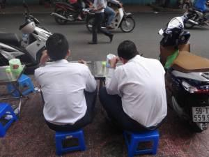 Vietnam | Süden, Essen vietnamesisch in Ho Chi Minh City. Zwei Männer mit Stäbchen essend von hinten fotografiert auf zwei blauen Hockern sitzend