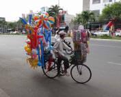 Vietnam | Süden, Straßenverkäufer von Ho Chi Minh City. Ein Mann auf seinem Fahrrad mit Luftballons und Kinderspielzeug zum Verkauf. Reise-Highlights & Tipps findest Du in unserem Reisebericht