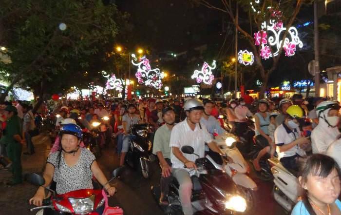Vietnam | Süden, Mopedfahrer von Ho Chi Minh City. Schlangen von Mopeds mit mehreren Menschen auf einem Moped bei Nacht mit bunter Weihnachtsbeleuchtung in den Straßen. Saigon-Sehenswürdigkeiten, Tipps & Highlights findest Du in unserem Reisebericht