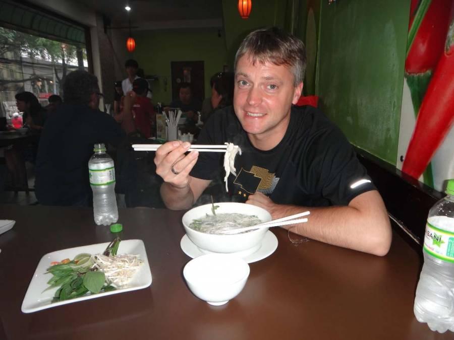 Vietnam | Süden, Pho24 in Ho Chi Minh City. Henning mit Stäbchen in der rechten Hand eine Nudelsuppe essend