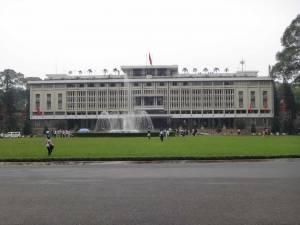 Vietnam | Süden, Wiedervereinigungspalast in Ho Chi Minh City. Blick von der gegenüberliegenden Straße auf das graue Gebäude des Palastes mit einer grünen Wiese und einem Springbrunnen im Vordergrund