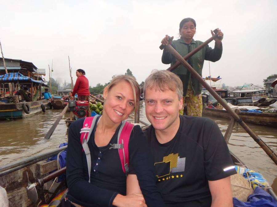Vietnam | Süden, Mekong. Floating Market Tour bei Can Tho. Karin und Henning auf dem kleinen Boot mit einer Einheimischen Bootfahrerin im Hintergrund inmitten schwimmender Märkte