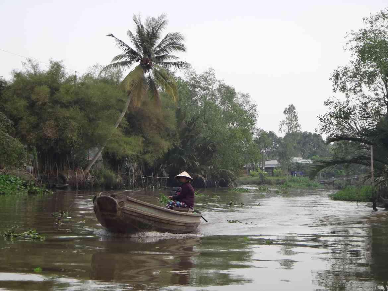 Vietnam | Süden, Fortbewegungsmittel im Mekong bei Can Tho. Eine Frau sitzt in ihrem Boot inmitten einer kleinen Nebenstraße des Mekong umgeben von sattgrünem Urwald