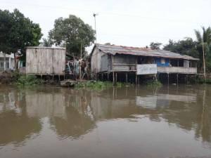 Vietnam | Süden, Leben am Mekong bei Can Tho im Haus auf Stelzen. Blick über die braune Brühe des Flusses auf ein schäbiges altes Haus