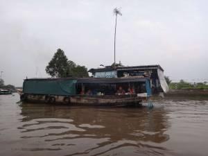 Vietnam | Süden, Frühstück an Bord auf dem Mekong. Blick auf ein Boot im braunen Fluss in dem Einheimische gerade frühstücken